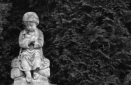 Lost in silent sorrow: A little mourner made of stone in Hietzing.