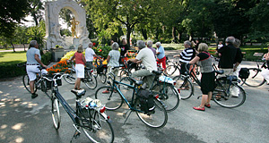 A group of tourists on bicycles explores the Stadtpark of Vienna - the Strauss memorial in the background